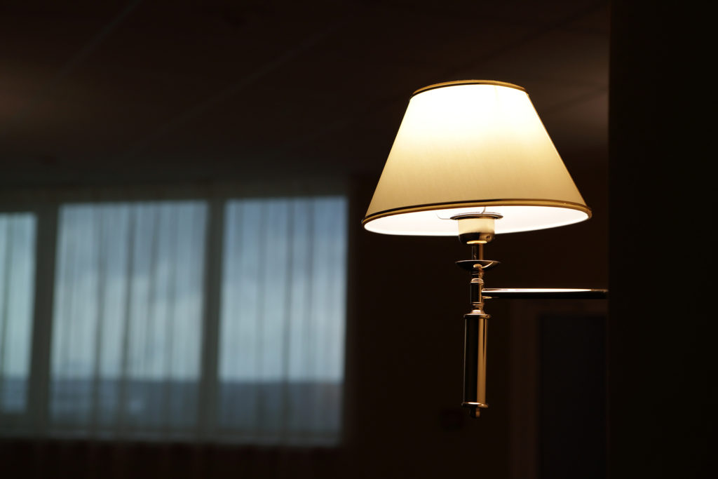 A stand lamp with the light on in a dark living room.