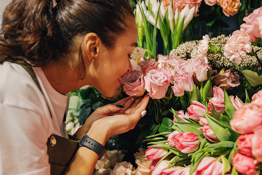 Image shows woman smelling flowers