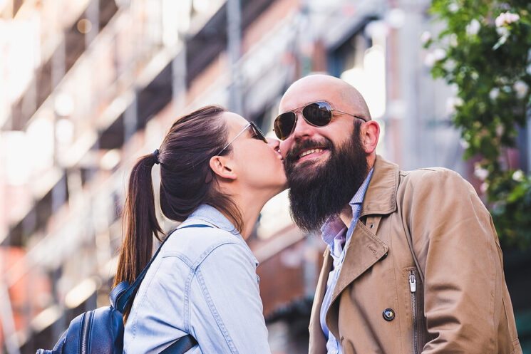 Image shows woman kissing face of smiling man