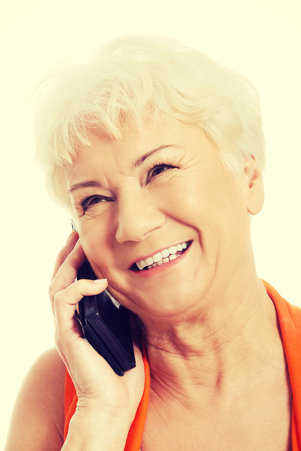 A woman smiling while talking on a mobile phone.