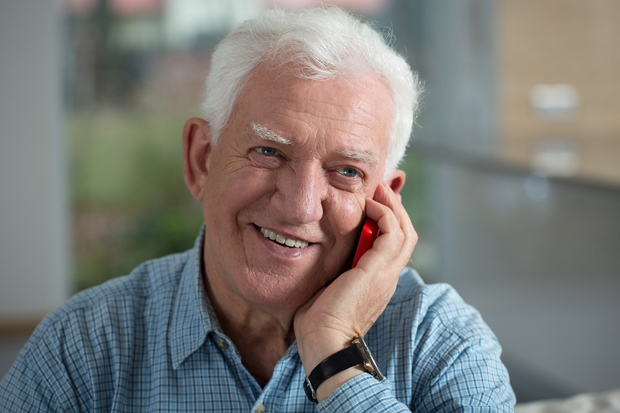 A man happy, while talking on a mobile phone.