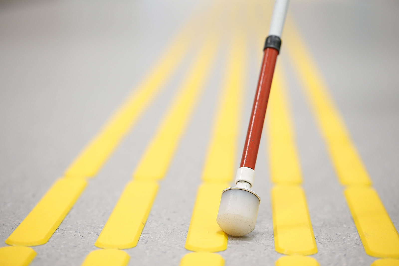 A close up of a long white cane on a street with yellow lines.