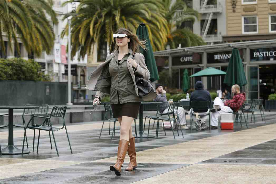 A woman walking while using eSight glasses in a city.