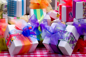 Wrapped gifts with different color bows on a table.