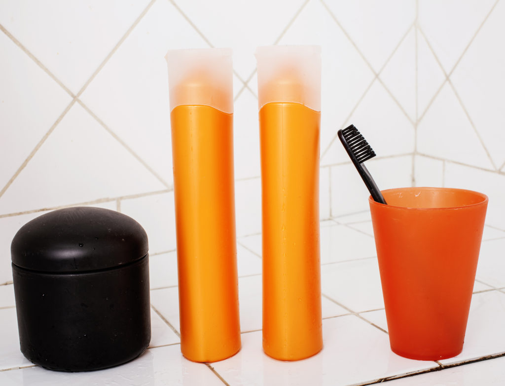 A toothbrush, shampoo bottles, and other bathroom vanities on a tiled background.