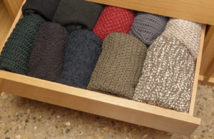 An organized drawer with folded clothing.