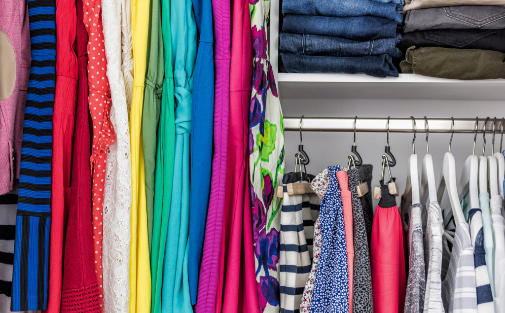 Colorful clothing organized in a closet.