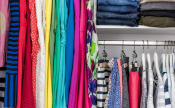 Image of colorful clothing organized in a closet.
