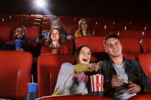 People sitting and excited, watching a movie in a movie theater.