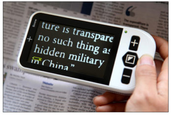 Portable video magnifier used on newspaper text.