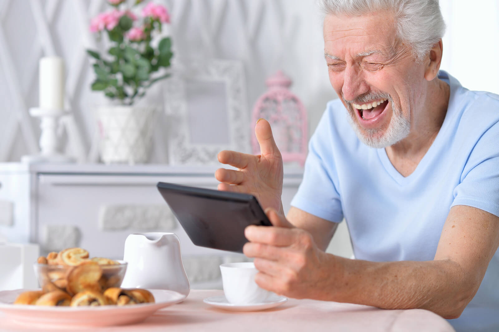 Older man happily using a tablet.