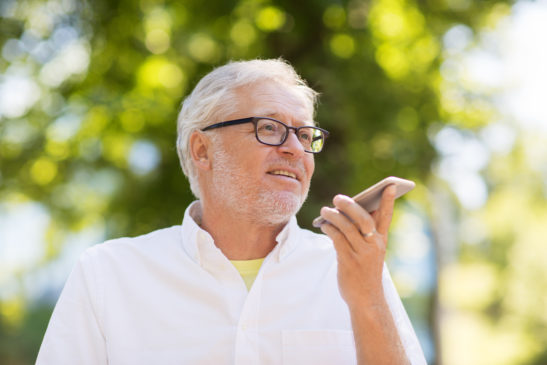 Older man using smartphone at park during the summer