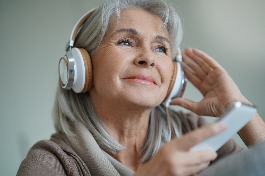 Woman at home listening to descriptive audio with smartphone