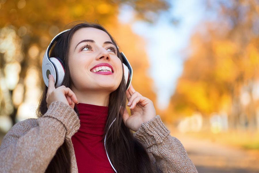 Young happy smiling brunette woman with headphones outdoors on autumn day.