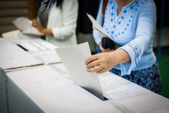 Image shows voter placing ballot in box.