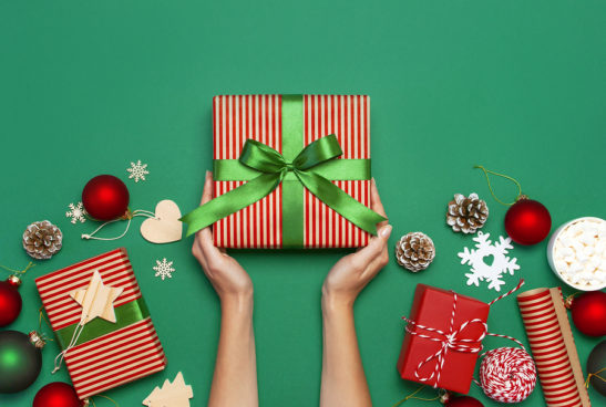 Hands holding present with Christmas gifts and ornaments around on a green background.