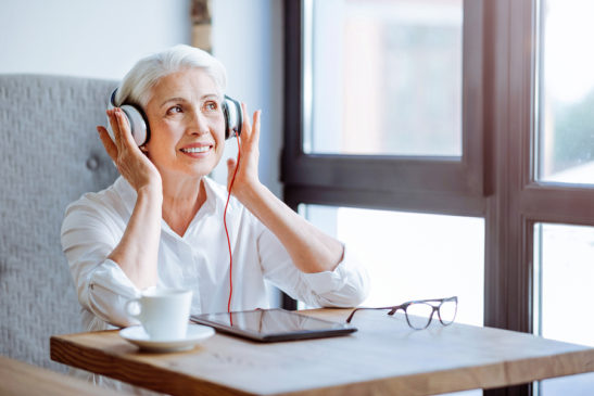 Cheerful woman with headphones listening to audiobook