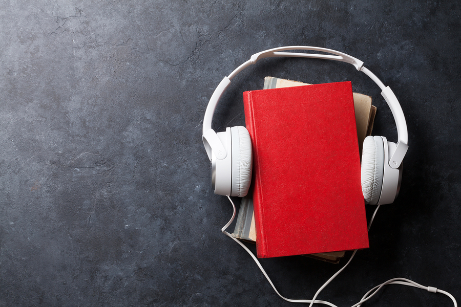 White headphones around red book on table