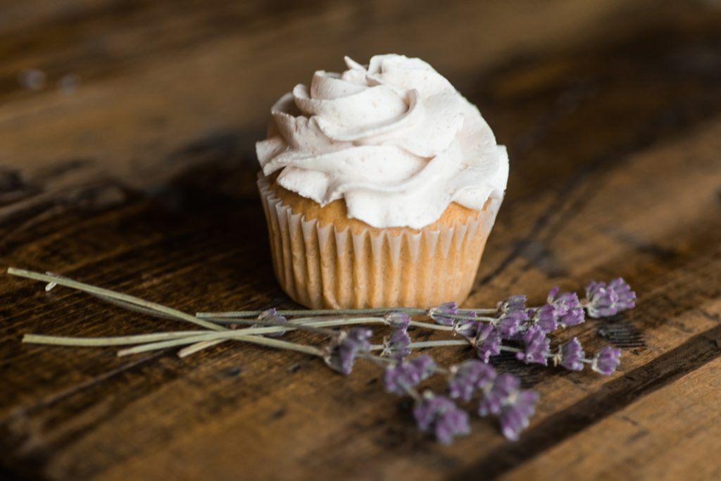 Cupcake with icing, next to sprigs of dried lavender, on a wooden table.