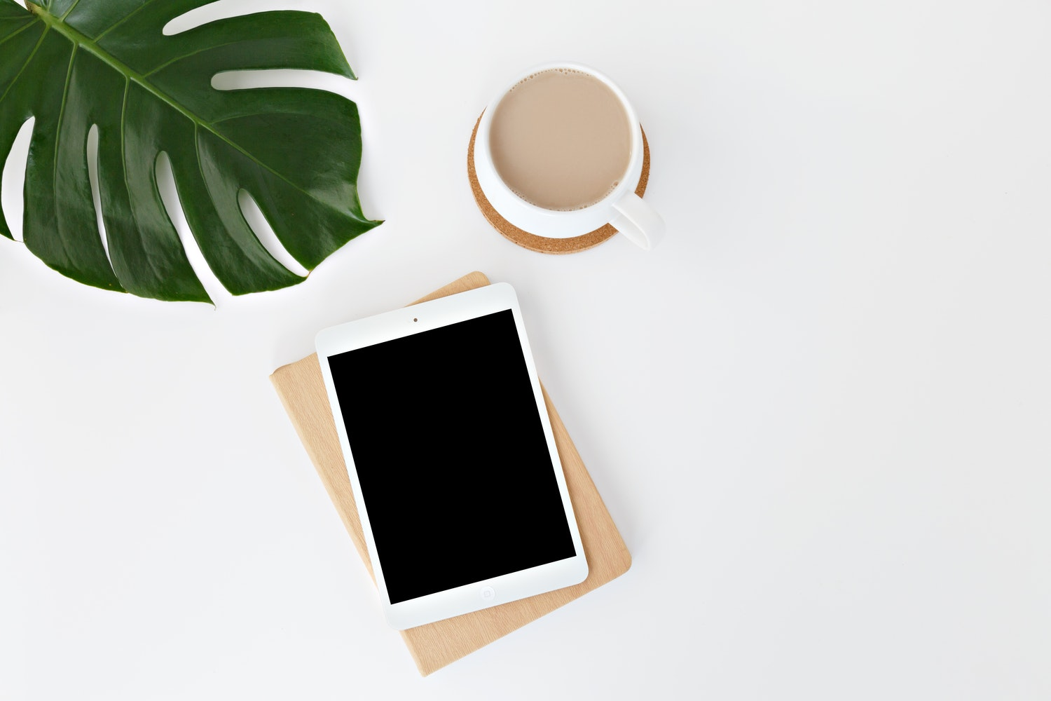 iPad with Coffee Cup and Leaf On a White Table