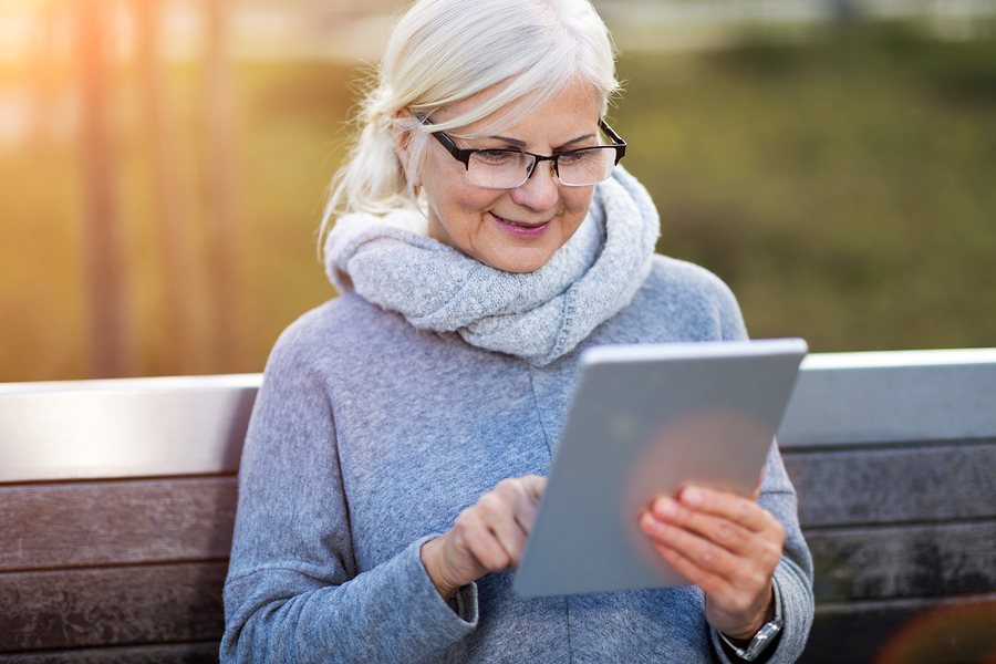 Older woman using digital tablet outdoors