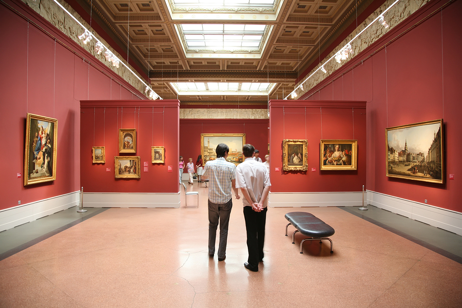 Museum visitors standing a red walled gallery lined with paintings.