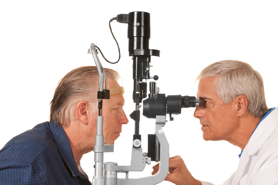 Ophthalmologist checking patient's eyes on white background.