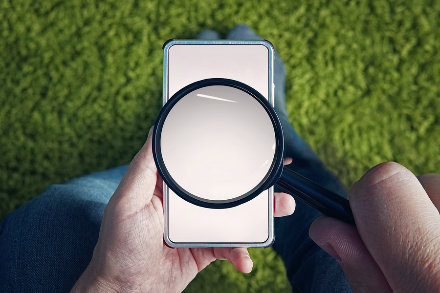 Man holding blank smartphone with magnifying glass above screen on grassy background.