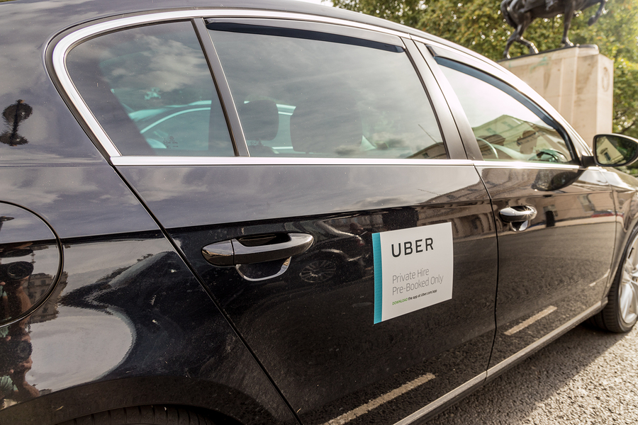 View of the left side of a black care with Uber sticker.