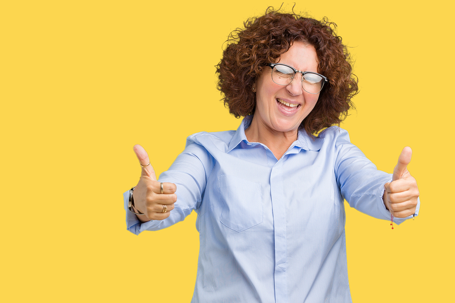 Happy woman wearing glasses giving thumbs up on a yellow background.