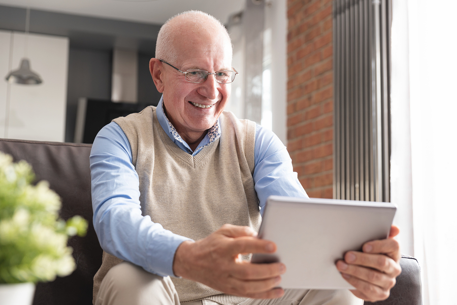 Senior man smiling while using digital tablet in living room.