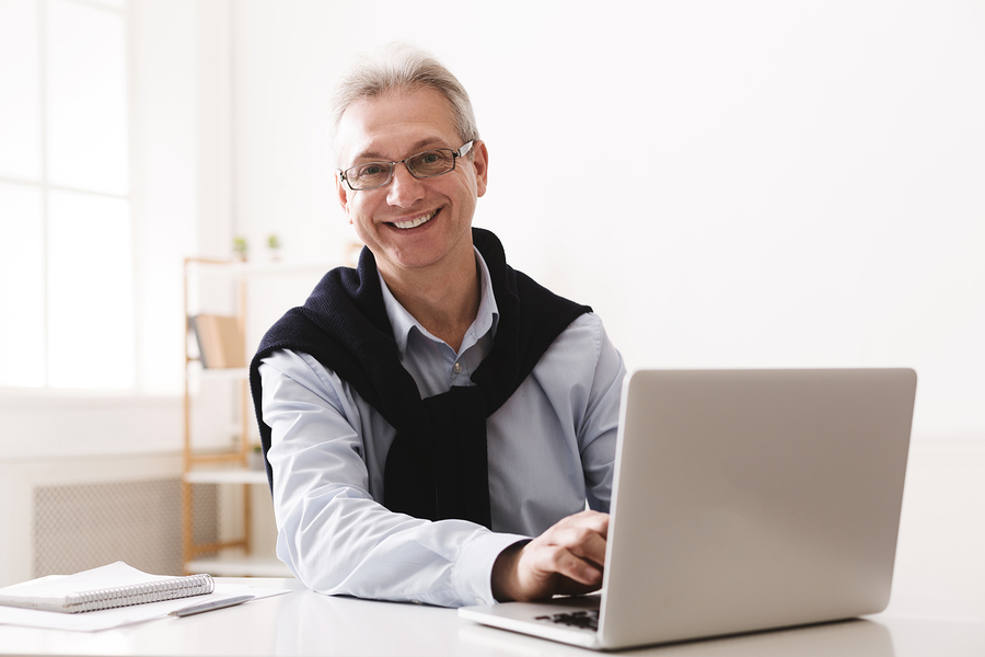 Happy Senior Man Using Computer at home office