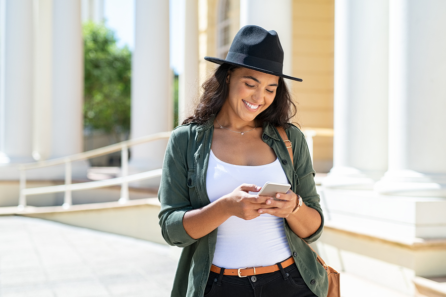 Happy woman wearing a hat using smartphone while traveling outside.