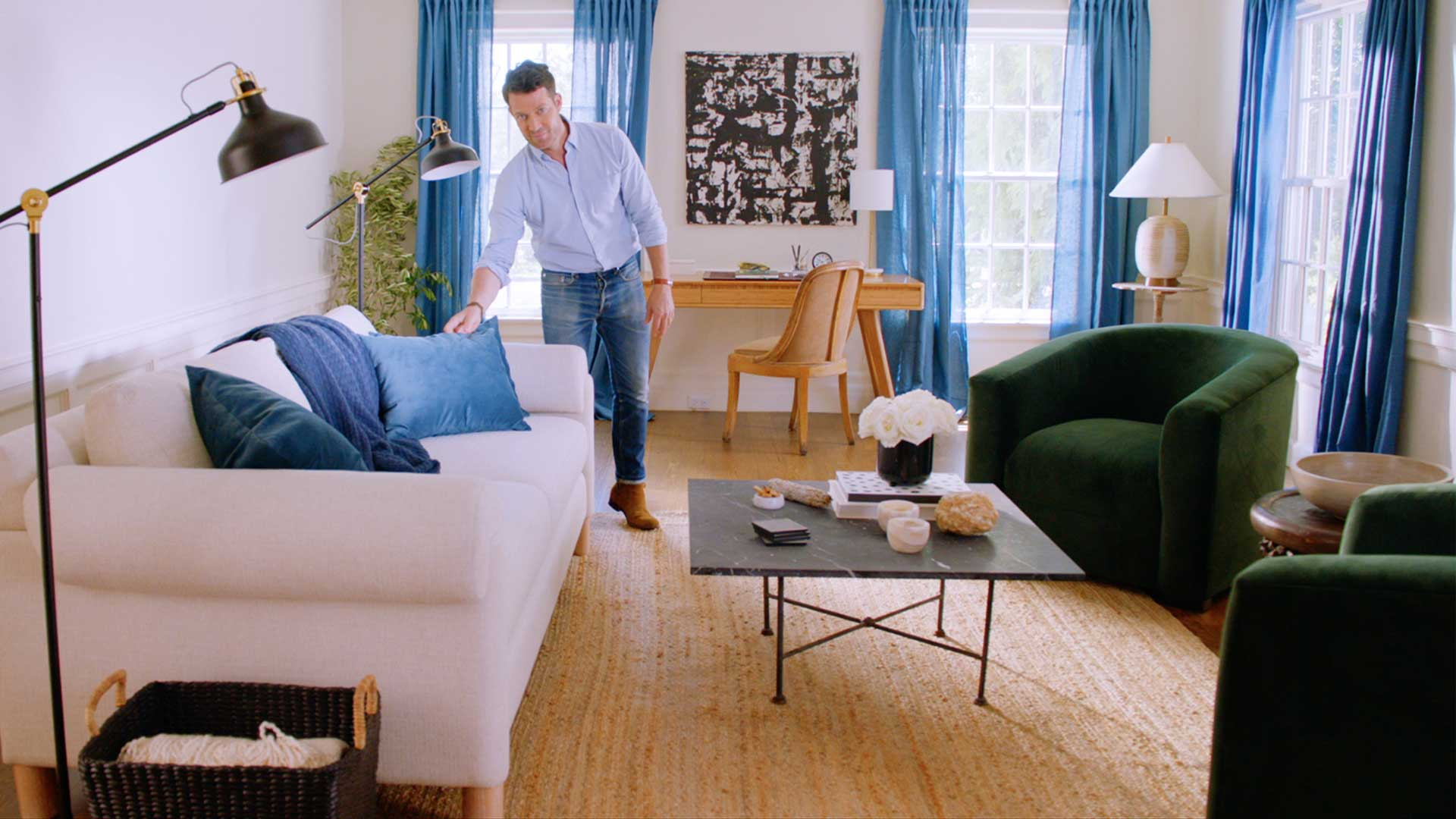 Nate Berkus fixing up a blue pillow on a couch in a living room.