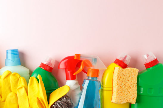 Colorful cleaning supplies on a light pink background.