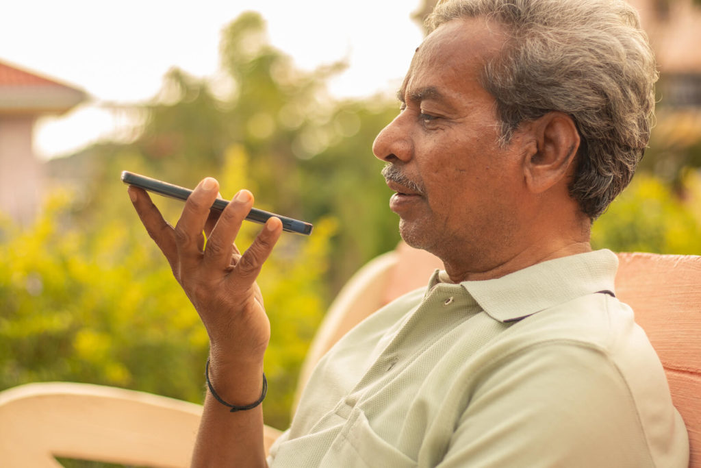 Senior man talking using smartphone voice assistant outdoors.
