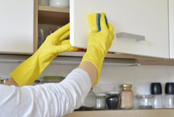 Image of hands in rubber gloves washing dishes.