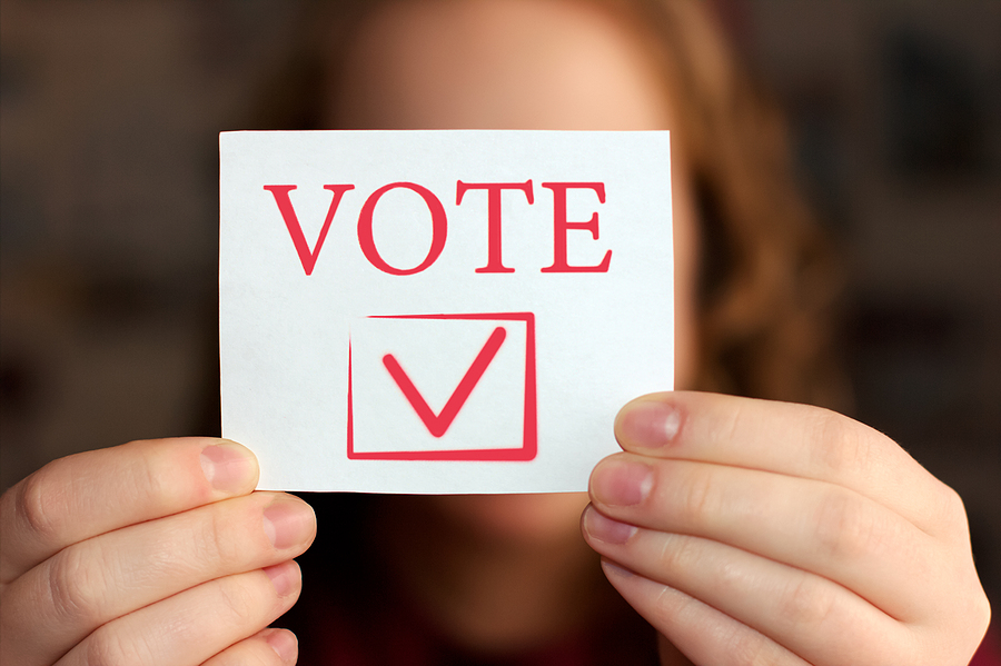 "Image shows: Hands holding envelope with ""VOTE"" printed on it."
