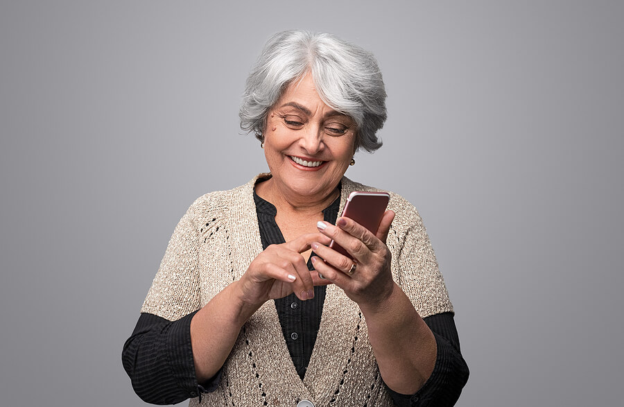 Savvy senior woman happily using smartphone.