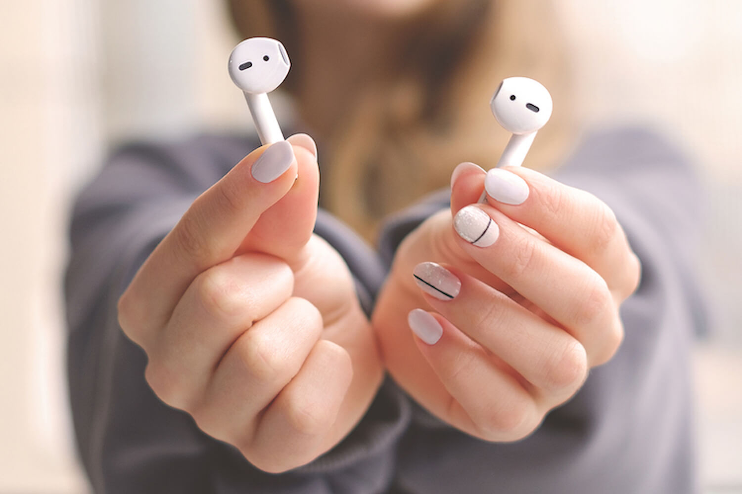 Hands holding AirPods.