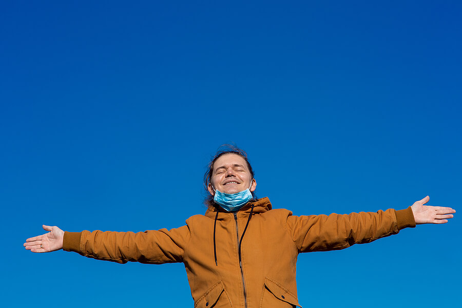 Image shows smiling man, arms outstretched, mask off face.