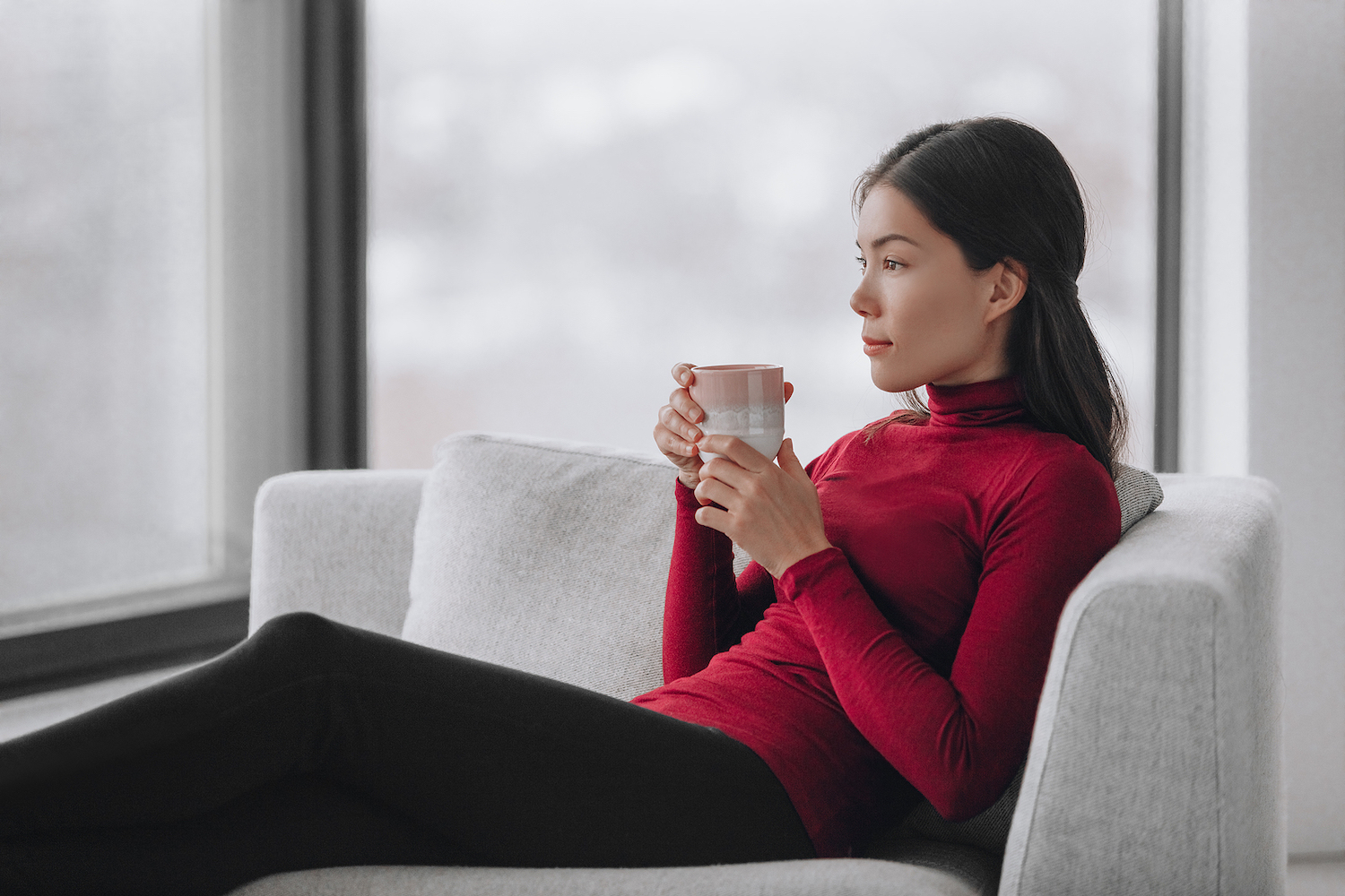 Image shows serene woman relaxing with a cup of tea.