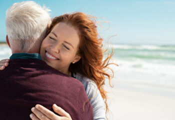 Image shows woman giving warm hug to loved one.