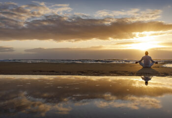 Image shows man in mediation at sunrise.
