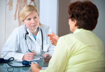 Image shows patient talking with primary care provider.