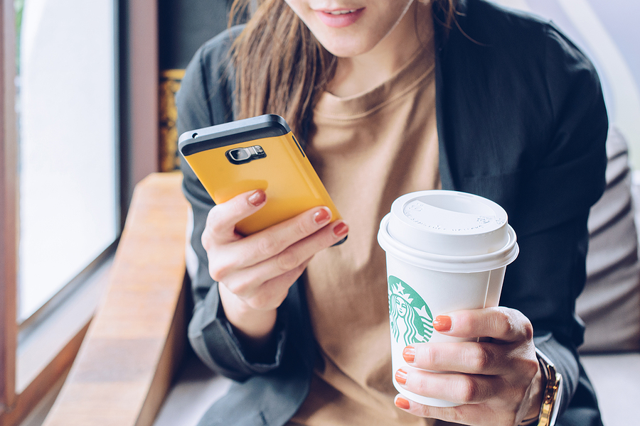 Image shows woman holding mobile phone and cuts of coffee from Starbucks.