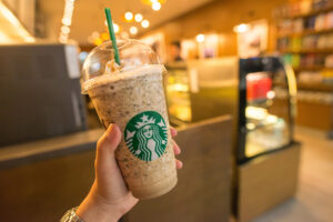 Image shows hand holding a triumphant Frappuccino