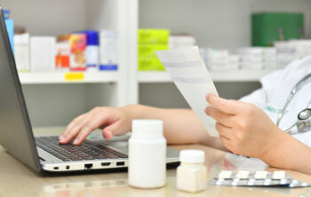 Image shows pharmacist at computer labeling prescriptions.