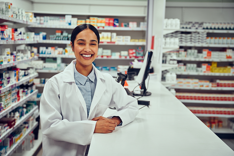 Image shows helpful, smiling pharmacist at work.